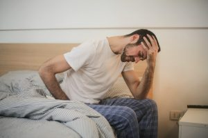 man sitting on bed feeling ill