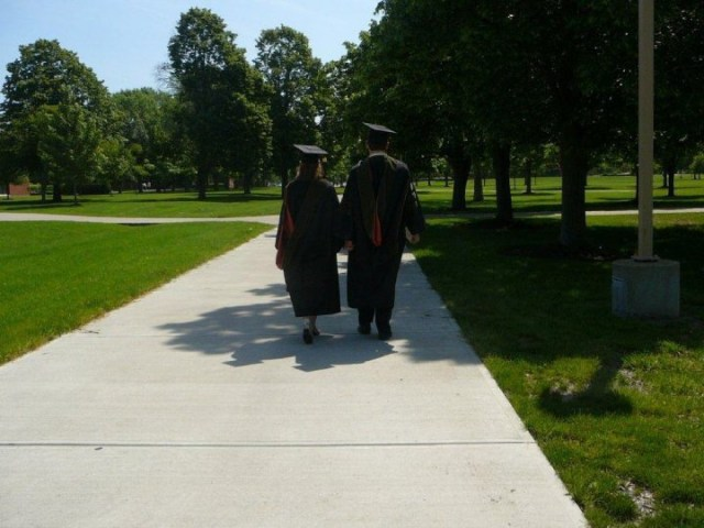 A man and woman wearing graduation cap and gown with doctorate hoods holding hands walking down a sidewalk away from the camera. The grass is green and the sky is clear blue.