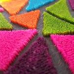Ricamo punto tappeto realizzato con filati fantasia e forme geometriche.