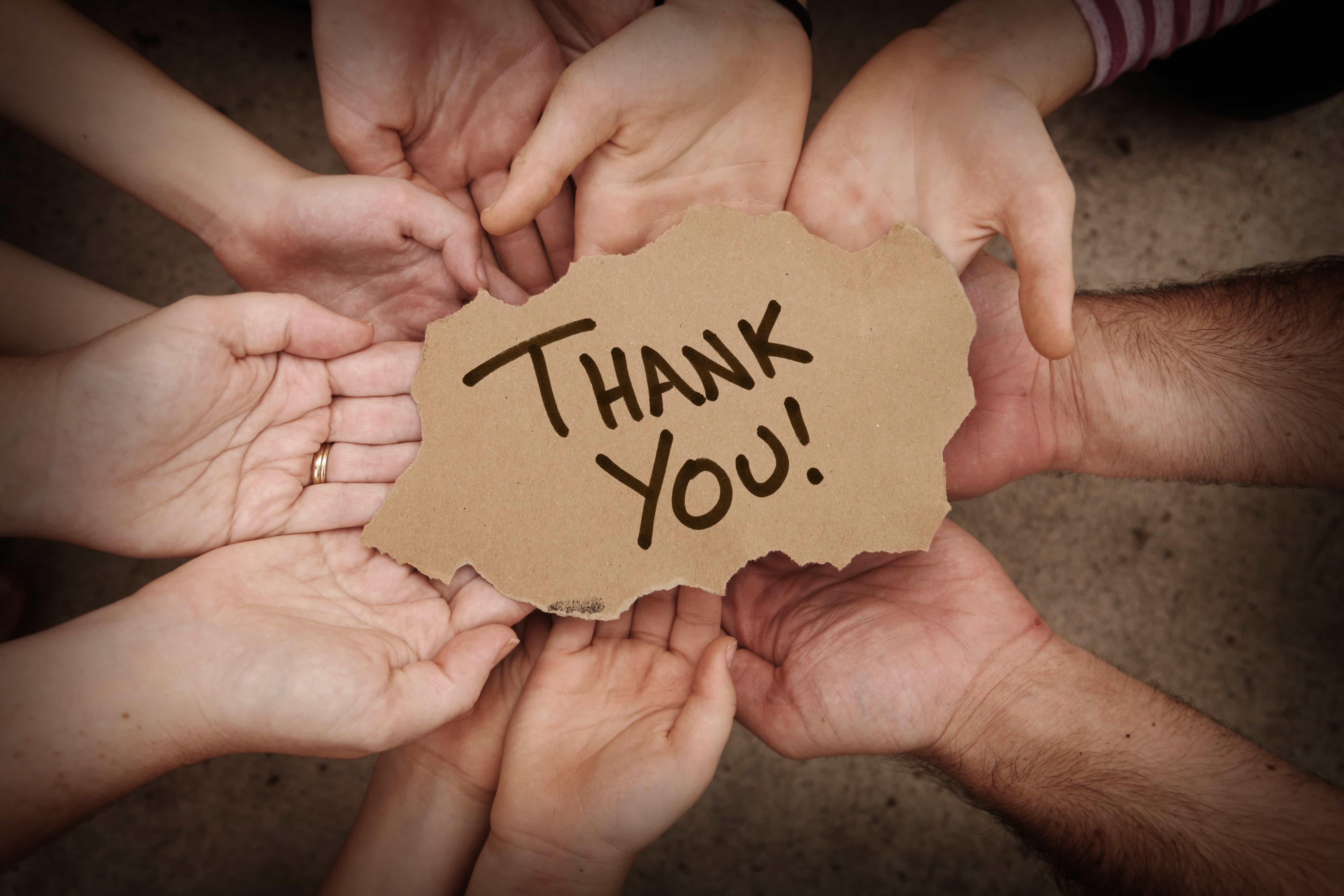 Thank You Written on Cardboard Being Held by Group