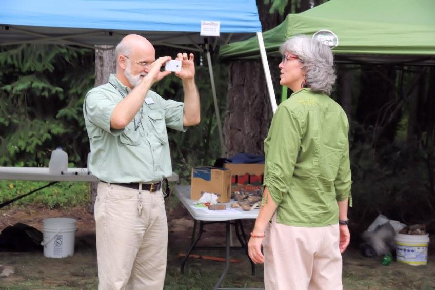 Julian Gray photographs exhibitor at Summer Fest.