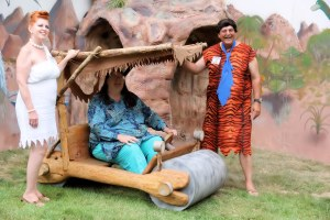 Fred and Wilma Flintstone and Summer Fest guest in Flintmobile.