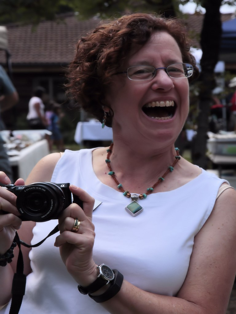 Volunteer Barb Epstein laughs and takes pictures.