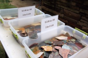 Rock slices for sale in water-filled pans.