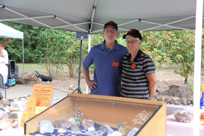Vendors pose by their exhibit of fine crystals and minerals.