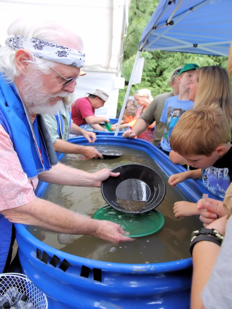 Rock Club volunteers and children pan for gold at Summer Fest.