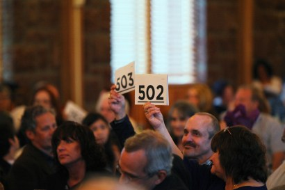 "A crowd of people seated in front of a window, mostly blurred. A man and a woman are in focus, holding up auction paddles with the numbers ""503"" and ""502""."