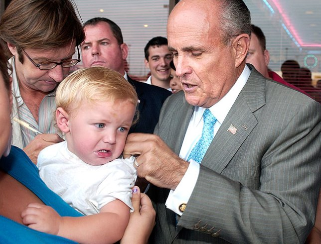 Presidential hopeful Rudy Giuliani signs an unhappy baby's blouse in Ada, spring 2007.