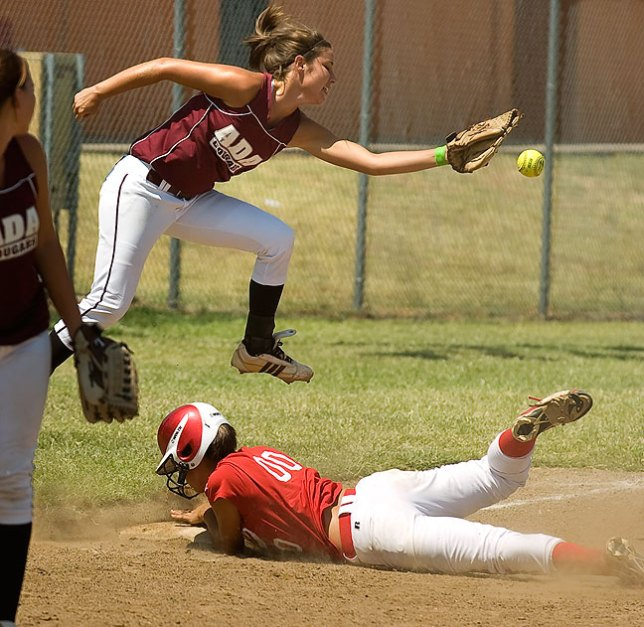 An Ada Lady Cougar softball third baseman leaps over a sliding McLoud Redskins base runner; either of these elements alone is only modestly interesting, but together they bring the viewer into the moment of conflict.