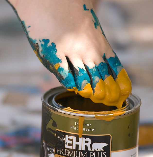 Trimble dips her toes into a bucket of paint to create an abstract painting in the Alla Prima style; she had her canvas spread on a sidewalk in a shady spot near the building where I teach.