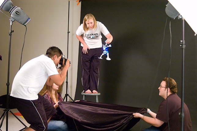 """Kelly, Chesna and Robbie work together in an effort to photograph the """"Nerd"""" toy in the studio Wednesday."""