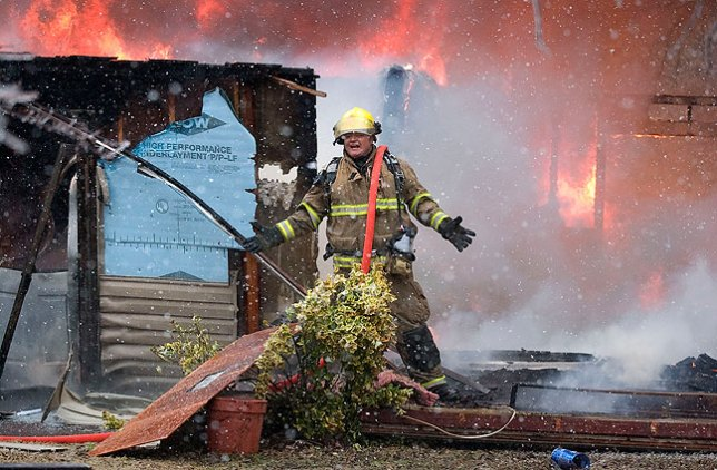 A firefighter waits for water at a fatality house fire northwest of Ada, 2010