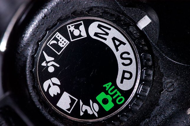 "In addition to the P, A, S, and M on this Nikon D80 exposure mode dial, there are a number of not very effective ""scene modes,"" like sports, portrait, landscape, macro, and so-on. Professional digital cameras don't include scene modes."