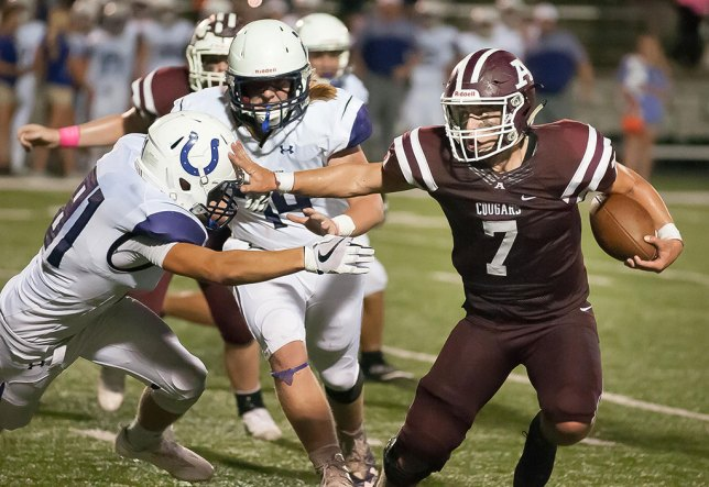 """Justin McFarlane stiff-arms an opponent in last night's game against Bethany. I was about eight yards ahead of the play, which came toward me. At 200mm with my 24mm x 15mm image sensor, the frame filled up nicely. The """"full frame"""" crowd was 30 yards down field, missing this image."""