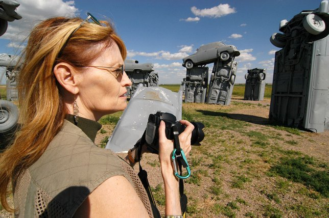 Abby scans the scene at Carhenge in Alliance, Nebraska for a photo with her then-new Nikon D70S in hand. She made a lot of great images with that camera over the years. Abby keeps a d-ring on the strap of her camera to clip to her belt loop to keep it from swinging when she hikes.