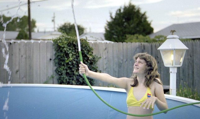 My sister Nicole plays with a garden hose as our new backyard pool begins to fill with water, July 1978.