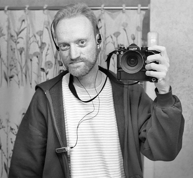 Film camera self portrait with headphones, circa 2000; of note is that the controller clipped to my hoodie is for a portable minidisk player.