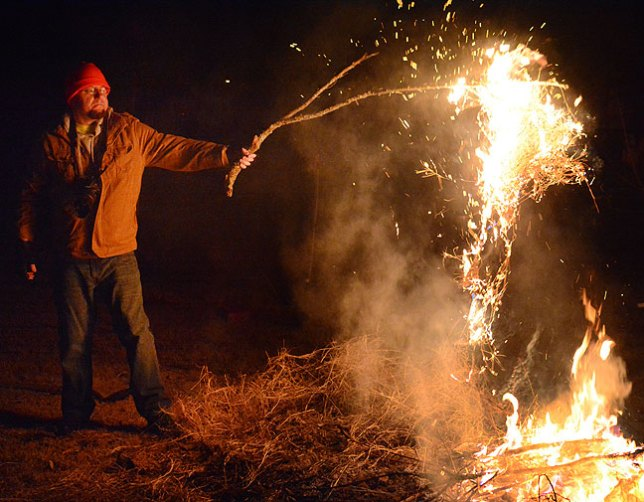 Dan Marsh lifts a branch full of dry grass from my fire last night.
