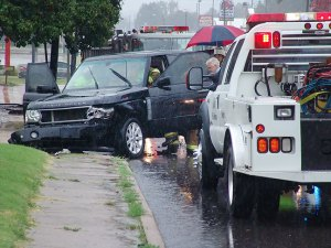 First responders attend to a traffic crash in the rain at 9th and Mississippi in Ada this morning.