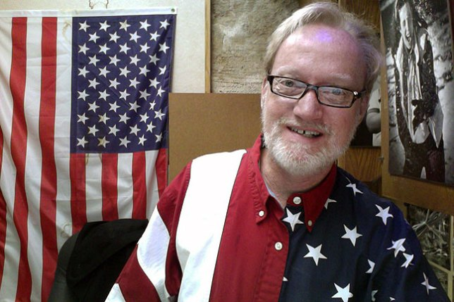 I am wearing one of my U. S. Flag shirts today. The flag behind me in my office is a permanent fixture. (Before anyone freaks out: those are reading glasses.)
