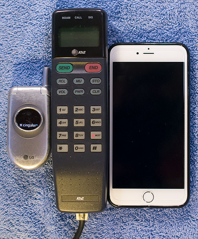 "The LG flip phone on the left was the smallest of all the phones we ever owned. The analog ""car phone"" from the 1980s in the middle of this image was the largest (it also had a large transceiver/controller mounted under the passenger seat. The phone on the right is Abby's current iPhone 6s."