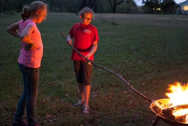 Hope and Harmoni roast a stick by the fire.