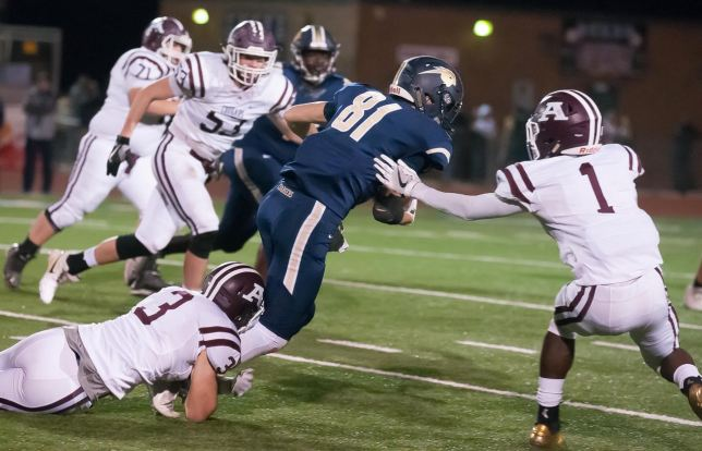 """Seniors Lincoln Gibson and Kylen Cooper bring down a Heritage Hall receiver Friday night. Kylen """"Coop"""" Cooper was a scoring machine all year long, but was completely shut down by the Heritage Hall defense."""