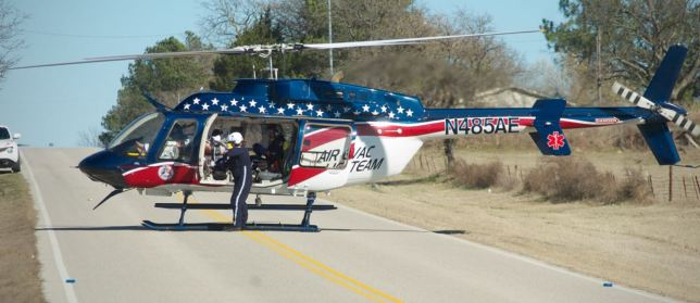An air ambulance prepares to lift off with one of three patients injured in a rollover accident northwest of Ada yesterday. My car is visible parked in a driveway at the left edge of the frame.