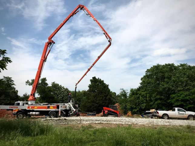 A crew uses a giant tube crane to deliver concrete to the piers on which our new cell tower, Nerdman's Pride, will roost.