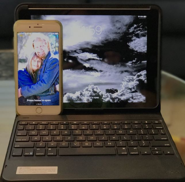 My iPhone rests on the screen of my iPad, which sits cradled in its Zagg case and keyboard.