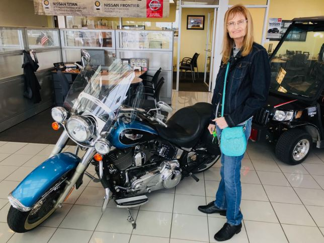 Abby smiles as we look at a Harley Davidson motorcycle at the Nissan place today while we waited for her truck to be serviced.