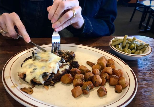 Abby digs into her Monterrey steak. I look at this picture and think what pretty hands she has.