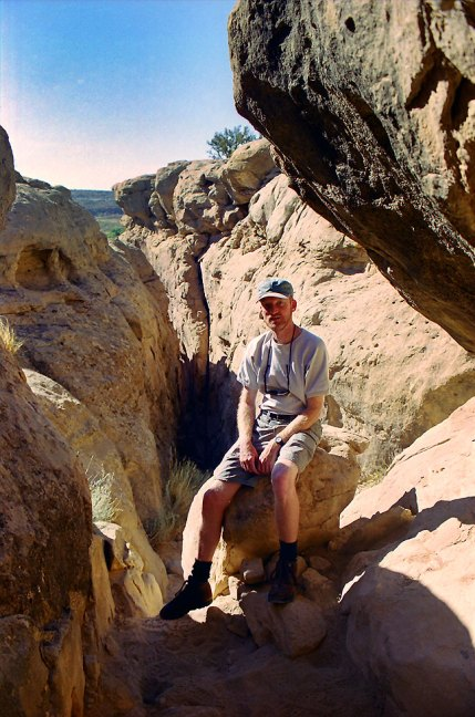 "Your host pauses for a photo as he climbed the ""crack"" at the start of the Pueblo Alto Trail at Chaco Canyon."