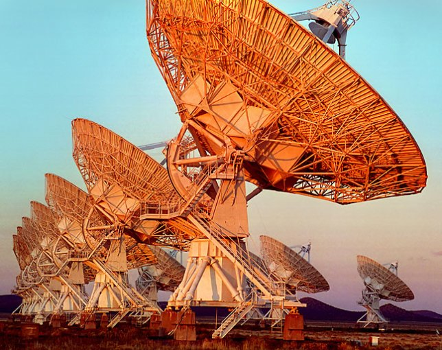 Radio telescope dishes of the Very Large Array near Magdalena, New Mexico, picks up golden light at sunset.