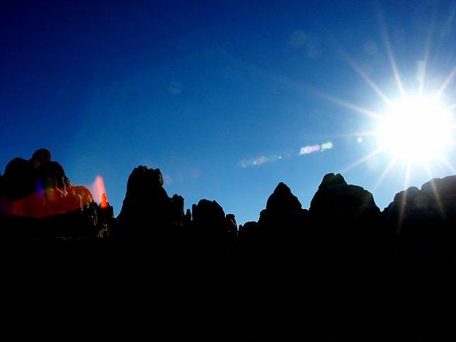 Brilliant late-afternoon sun shines through pinnacles near the Chesler Park trail head.