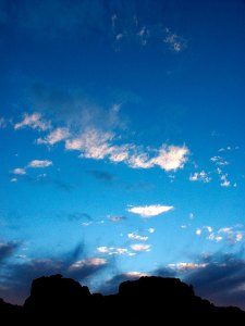 Wisps of clouds swirl in the breeze above the Squaw Flat Campground at dusk.