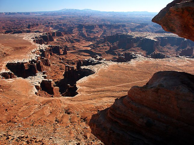 This image shows Monument Basin from the White Rim Overlook with the Abajo Mountains in the distance.