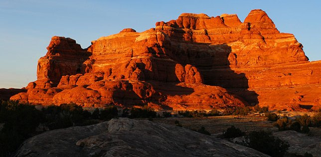 Squaw Butte at Canyonlands takes on red light at sunset.