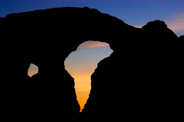 Turret Arch is silhouetted against the sky after sunset at Arches National Park.