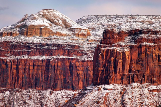 A light dusting of snow clings to Wingate Sandstone cliffs above Indian Creek.