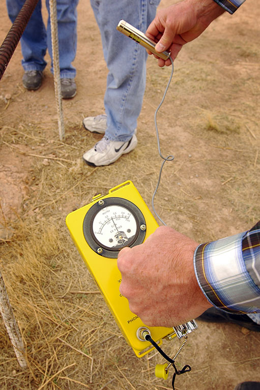 A man uses a geiger counter to measure remnant radiation at the Trinity Site.
