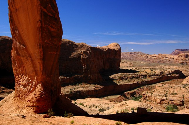This view from directly under Corona Arch looks west toward the trail head. The cut for the rail line is visible.