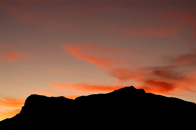 The sky lights up amber hues after sunset on El Capitan and Guadalupe Peak.