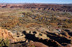 The City of Moab, Utah is laid out before visitors to the Moab Rim, with Arches National Park on the horizon.