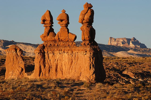 This is The Three Sisters formation near Goblin Valley. In the distance is Temple Mountain.