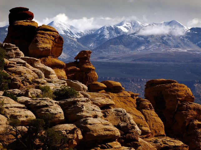 Sandstone formations stand in the foreground with the La Sal mountains in the background. The La Sals are a signature formation in for the Moab, Utah, area.