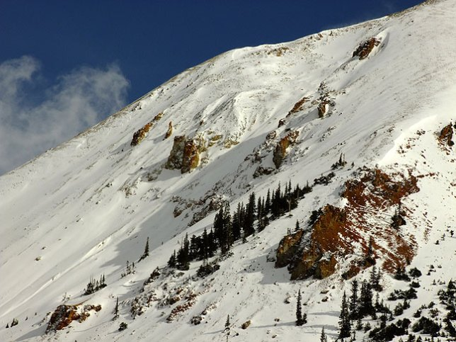 "Snow clings to the steep slope of a 14er in the San Juan Mountains of Colorado along the ""Million Dollar Highway"" between Ouray and Silverton, Colorado."