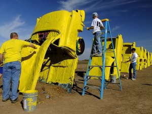 LiveStong volunteers paint Stanley Marsh's Cadillac Ranch.