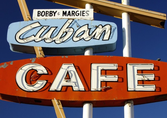 A café signs in Cuba, New Mexico stands in magnificent autumn sunshine.