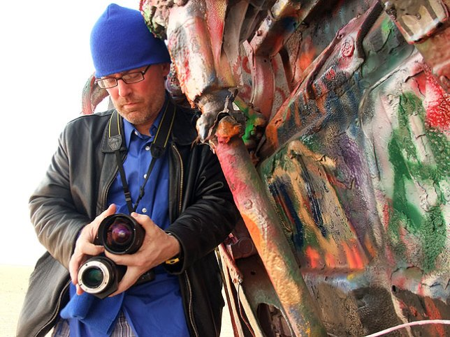 Happy to be shooting Amarillo's colorful Cadillac Ranch, Robert struggles to change lenses while hiding from a stout, dusty wind.